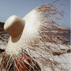 Sophisticated variation of the classic beachcomber sun hat with extra long pieces of straw extending from a downward facing brim to form a fringe.