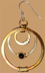 """Hoops and Sticks   This hand formed red brass, nickel silver and copper hoop earring is wrapped and finished with a black onyx stone. This heat patinaed earring hangs freely from a sterling silver wire. 1 7/8"""" x 1 7/8"""". Handcrafted by Whitney Sarasota.   Our Price $48.00 Pair   Item # E1521"""