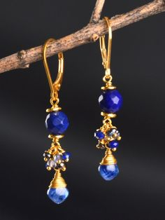 Lapis, Kyanite, and Peacock Pearls are beautiful colors for an every day cluster earring, and these transition through every season.At the top, a silver or gold vermeil beads frame a round, faceted Lapis. Below,a cluster of iolite, peacock pearls, and lapis bring a playful movement. Dangling at the bottom,a smooth, diamond shaped Kyaniteis spiral wrapped in fine detail.  The Asteria Cluster Earrings were designed in sterling silver and 22kt gold vermeil. As pictured on leverbacks…