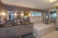 Motorized Vignette® top/down bottom/up Modern Roman Shades shed new light on this bathroom model while also offering a brilliant privacy solution. ♦ Hunter Douglas window treatments