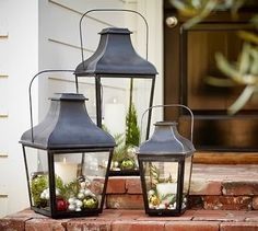 trio of Pottery Barn lanterns decorated with Christmas ornaments - front porch decor
