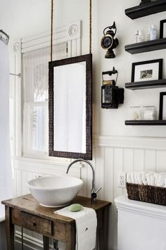 How to decorate around a window! Perfection! Unique bathroom mirror hung from the ceiling brings a rustic vibe to the space. Open shelving and vintage light fixtures and elements complete the look.