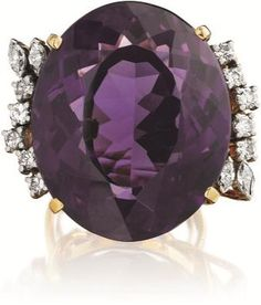 Amethyst and Diamond Ring Centering upon an oval-cut faceted amethyst, weighing approximately 34.00-36.00 carats, enhanced by circular and marquise-cut diamonds, mounted in 18K yellow gold