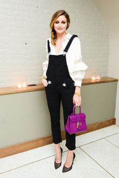 Olivia Palermo looking casually cute in black overalls, classic pumps, and bright mini-bag