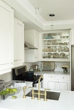 source: Sarah Richardson Design Glam U shaped kitchen with creamy white kitchen cabinets, beveled marble countertops, open shelves with mirrored backsplash, and Saltillo Imports Marble Mosaics Long Octagon Tiles backsplash.   Para Paints Whitecap