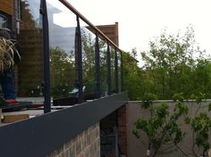 Laser profile design glass balcony balustrade with iroko timber handrail. Powdercoated steelwork in RAL 7015.