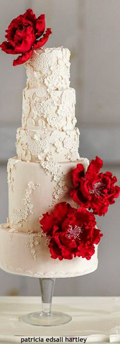 Gorgeous white wedding cake with red flowers More