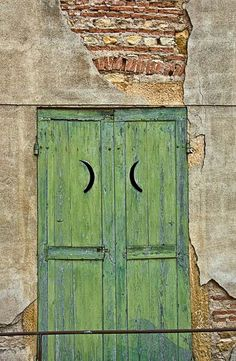 green door with lunar peep holes