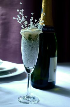 For restaurants or bars, the floral version of a 'glass of bubbly'.  Champagne glass filled with acrylic crushed ice, rose and crystal sprays