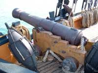 This photo shows what a deck cannon would have looked like in the 18th century. The cannons mounted below decks would have been mounted in similar carriages but with a less extreme angle on the muzzle.