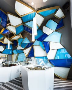 jean de lessard wraps Némeau seafood shop in quebec city.  The key aspect of this element is the extraordinary bookcase aboard the Nautilus that Jean de Lessard has conceptualized and successfully integrated in his design. In one fluid motion, the striking honeycomb ceiling becomes a sweeping tsunami of shelves. This is a simple, practical and ingenious way to maximize the store area surface.