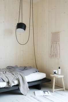 The AIM pendant light by Ronan and Erwan Bouroullec completes the aesthetic in this minimalist modern bedroom with a neutral color scheme and pale wood walls.