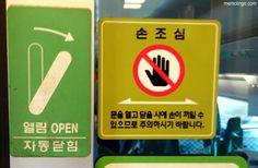 Dos carteles en el tren rápido coreano KTX que piden precaución al usar las puertas para no hacerse daño en las manos.
