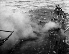 Crews aboard USS Enterprise controlling fires from a Japanese bomb that blew the forward elevator completely out of the ship off Kyushu Japan 14 May 1945.