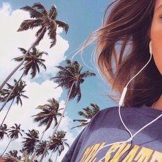 chica camninando en la calle y palmeras audifonos
