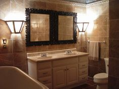 So as we turn to show the L portion of the bathroom you see my sconces, some beautiful hand carved mirrors, and the vanity with a cultured marble double sink. You can also see the toilet tucked away in the...