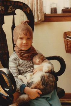 """""""This is me and my cat, Keke. Words cannot describe the torture I put that cat through. She lived to be 22 and would follow me around for some reason."""" (submitted by Isaac)"""