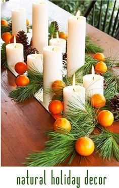 natural holiday decor with candles, greens, and clementines