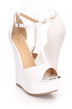 Doll up any outfit with these stylish wedges! They will look super hot paired with your favorite skinnies or dress. Make sure you add these to your closet, it definitely is a must have! The features include a faux leather upper with a T strap center, ankle strap with a side buckle closure, peep toe with a high polish trim, smooth lining, and cushioned footbed. Approximately 5 3/4 inch wedge heels and 1 1/2 inch platforms.