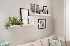 A parede segue a linha de decoração proposta pelo abajur e pelas almofadas. Para isso, trabalhamos com duas prateleiras em desnível. Alterando entre plantas, velas, enfeites e diferentes estilos de quadro, ela dá movimento e personalidade à sala de estar pequena.