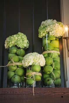 Green apples and hydrangeas in centerpiece glasses.