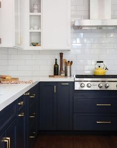 Love the white pearl tiles, gold handles and yellow kettle to complement this white & navy kitchen