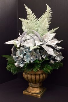 Holiday 2014 Season Faux silver and glitter poinsettia, powder blue pearl hydrangeas and glitter sea-foam fern on pine filled golden urn. Original design and arrangement by http://nfmdesign.synthasite.com/
