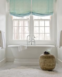 Bathroom with freestanding tub, marble tiles floor, white flokati rug and green roman shades.