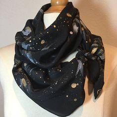 Stardust and sparkles sprinkle all along this rich black silk crepe de chine scarf. Bursts of pearl white and gold metallic brush strokes strike a perfect contrast against the midnight background. It has just enough shine to catch the light as you twinkle on by. Perfect for any special occasion or just being the shiny you that you are! The crepe de chine has a very pretty sheen and is light enough to float in the breeze. Measures 11x58 Want to see more scarves from Muse? http://ww...