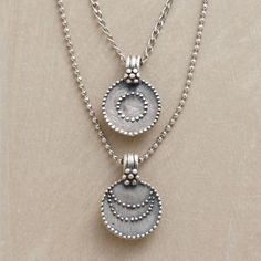 SILVER LUNA/SOL NECKLACE--This silver sun and moon necklace displays two granulated sterling disks—one emblazoned with a sun, the other with a moon—suspended from two chains of different lengths