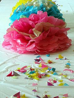 tissue paper pom pom centerpieces. great idea to use the cut off pieces as table confetti.