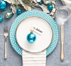 Try an icy blue and silver color palette. For the name card, tie a store-bought tag to a metallic glass ornament.  Dinner plate, $28, jonathanadler.com. Salad plate, $25, canvashomestore.com. Napkin, $8, katespade.com. Wineglass, $32 for four, westelm.com. Silverware (similar), target.com. Ornaments, etsy.com.  - GoodHousekeeping.com