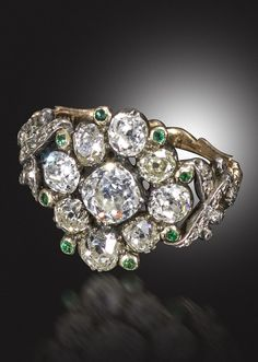 A George III diamond and emerald cluster ring, centred with a cushion-shaped diamond within a surround of eight smaller cushion-shaped diamonds and eight small emeralds in silver and gold, the open work scroll shoulders set with further diamonds and joining the gold shank with inverted heart shapes, engraved to the interior with Hebrew inscription translating to Yevarechecha Adonai v'yishmarecha (May the Eternal one bless you and watch over you)