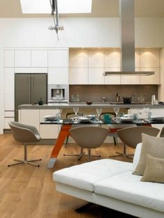So if we can't orient the kitchen to the living area without creating a u-shaped kitchen, then maybe we elongate the kitchen and have it be very open like this one. Really like the white cabinets, the concrete surfaces, and would like to add small wooden inset boxes in place of some of the square cabinets. Also, might use open shelfing instead of cabinets for above the counter on the back wall.