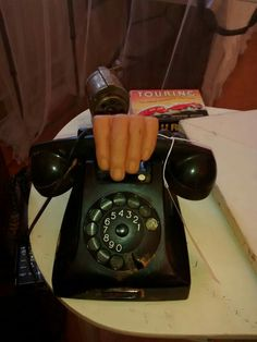 For my Halloween booth at a Vintage Country Flea Market I put a rubber hand on the receiver of this old art deco Bakelite phone.
