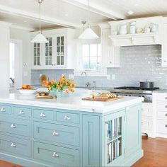 Painted island with white cabinets.