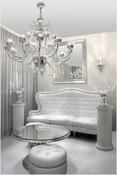 White tufted couch. Silvery-white walls. Huge silver chandelier. Mirrored table. White floors. Perfection.