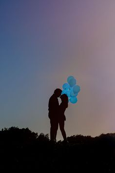 gender reveal, it's a boy, blue balloons and silhouette of the couple.