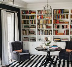 Blue & white office den design with blue walls paint color, blue velvet tufted wingback chairs, round black table, white & black striped rug, lantern pendant, white drapes, white, built-ins, bookshelves cabinets and silk orange & yellow striped pillows.