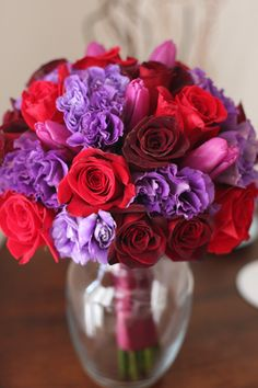 purple tulips, purple lisianthus, red roses in dark and true red