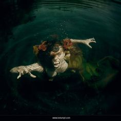 Photo of a scary evil mermaid attack in the cenoted cavern and freshwater cave system of Playa Del Carmen, Mexico. Redhead mermaid / siren wears a flower headdress, tail, and fangs while hunting in swampy water. Underwater photography art by Brenda Stumpf. Model Jessica Dru. See more at www.sheroesentertainment.com // www.facebook.com/sheroesentertainment // www.facebook.com/themermaidproject