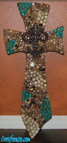 "Cross, custom made. This cross is unique with rock pieces, clear and teal beads that really add color to this great piece. The center is accented with a iron fleur de lis. Great for any home! Dimensions are 13"" wide x 30"" long $65.00, also comes in larger size 13"" x 42""."
