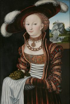 Portrait of a young lady holding grapes