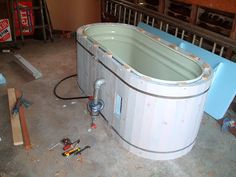 Stock tank hot tub - could use shipping pallet wood to enclose the stock tank.