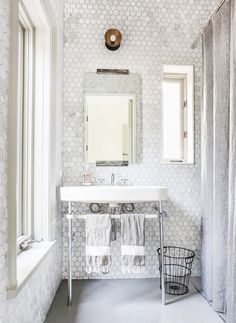Tiled bathroom with lots of bright white shades and neutral face towels