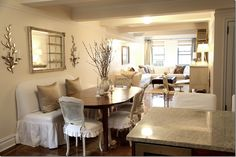 Such a charming dining area carved out of this long NYC apartment. The banquette is slipped in oyster linen.  Chairs are Shabby Chic, slipcovered Darcy.   The pillows are by Michele Varian.   Sconces by Oly.