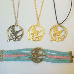 Hunger Games Mockingjay Necklace Bracelet Hunger games mockingjay necklaces and bracelet  you pick: silver, gold, gold on black cord or bracelet. $10 each, 2 for $15, 3 for $20 or all 4 for $25  (ALL ARE BRAND NEW NEVER BEEN WORN) Jewelry Necklaces