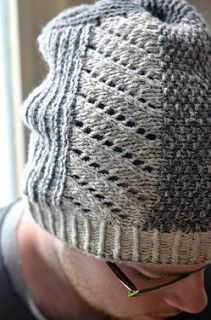 Fingering weight yarn is held double in three colors for a worsted gauge and marled fabric effect. The hat's body is worked sideways in diagonal lace, corrugated ridges and seed stitch. The brim and crown shaping are worked in the round with twisted ribbing and garter stitch. Wear the hat pushed back with slouch or fold the brim for extra warmth on the ears.