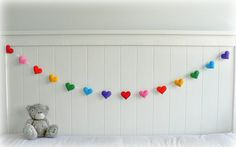 This beautiful hearts bunting/ garland/banner is completely hand cut and hand stitched by me with white thread, 7 (14 total) bright, rainbow colored eco-friendly felt hearts in red, pink, orange, yellow, green, blue and purple and threaded with a sheer white ribbon. Each heart has been stuffed with hobby fill to create a cute plump effect. Each side has extra ribbon so you can adjust the length and each heart is movable along the ribbon so you can make the gaps smaller or bigger in between…