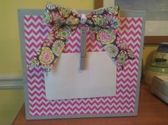 First, I got Home Depot to cut a long thick board into square feet. I then  used gray spray paint to lightly cover the wood. I used Hobby Lobby chevron scrapbook paper and modge podged it onto the board. Hobby lobby ribbon was then made into a cute bow and hot glued at the top. Finish it off with a hot glued clothespin to hold a 4x6 picture. Picture frame stands up on its own! Super cute!